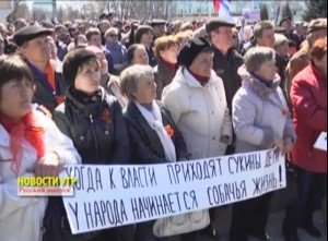 """Protesters in Luhansk holding a sign that reads: """"When SOBs come to power, the people are faced with a dog's life."""" Photo taken from Ukrainian Radio and Television via Wikimedia Commons"""